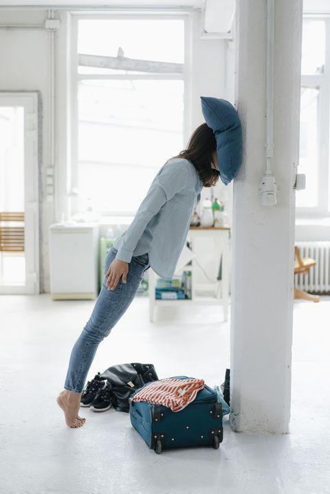 jet legged woman leaning on pillar