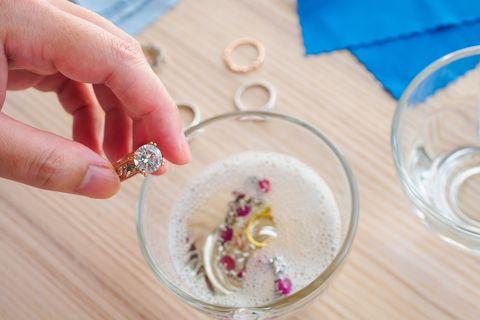 jeweller hand cleaning vintage jewelry diamond ring closeup