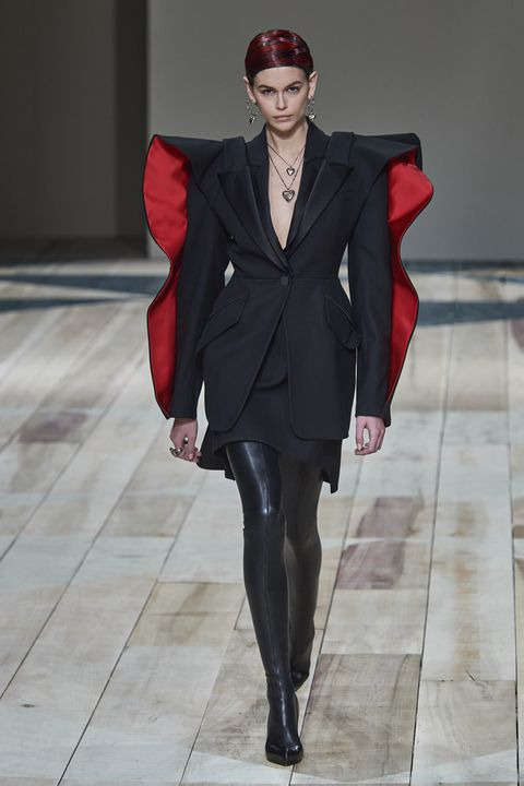 Kaia Gerber walks down a runway wearing a graphic black blazer, featuring red poofy embellishments on the sleeves. The outfit is style with tight leather pants.