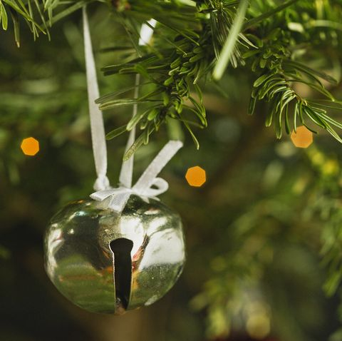 jingle bell ornament hanging from a christmas tree