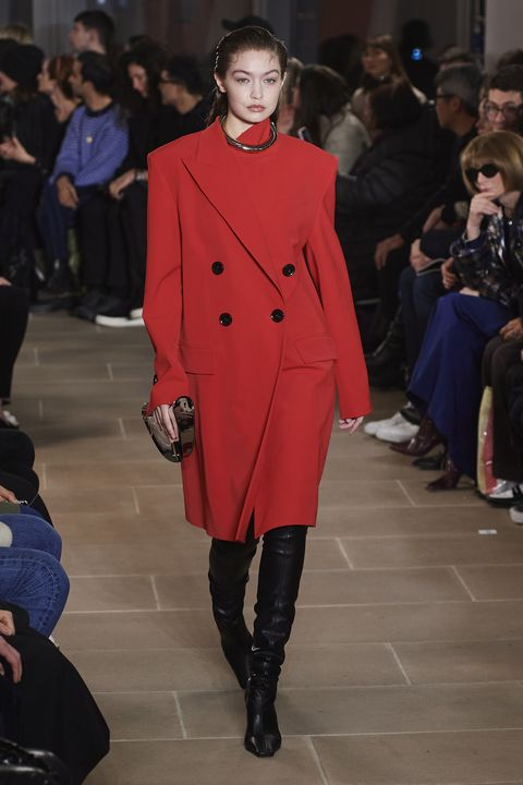 Gigi Hadid walks down a runway in a bold red trench coat with black buttons. She carries a reflective clutch and wears over-the-knee black leather boots.