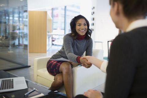 Businesswomen handshaking in office lobby