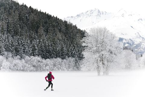 Jogger running in snowy forest