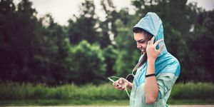 Jogging Girl With Earbuds and Rain Jacket Looking at Cellphone