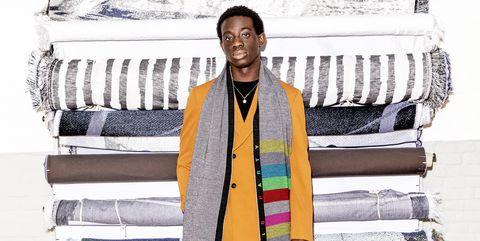 een jongeman gekleed in pak voor een stapel stoffen, met een sjaal om