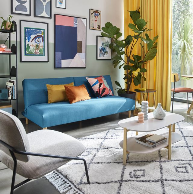 living room with a feature wall, blue sofa, marble coffee table and soft rug