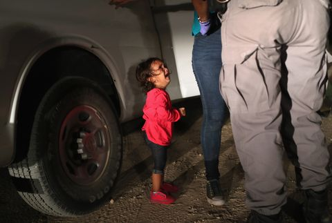 A two-year-old Honduran asylum seeker cries as her mother is searched and detained near the U.S.-Mexico border in McAllen, Texas.