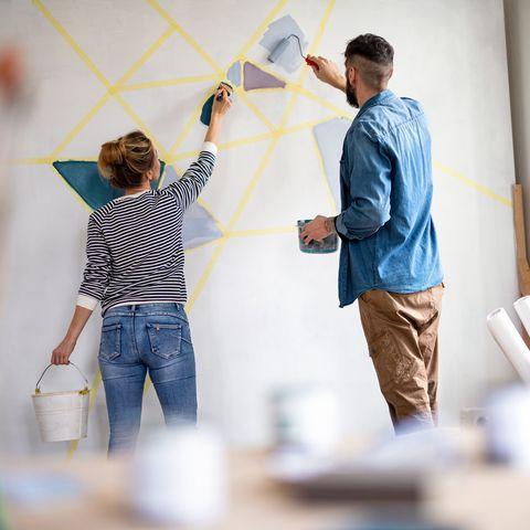 colocation, vue arrière d'un couple d'adultes moyens peignant le mur à l'intérieur à la maison, déménagement et concept de bricolage
