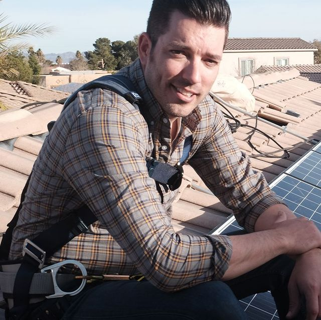 jonathan scott sitting on a roof with solar panels