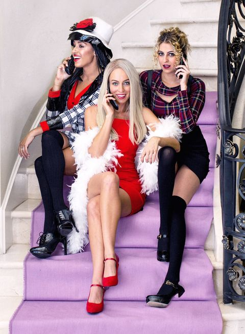 """three women sitting on stairway talking on cell phones dressed as characters from the movie """"clueless"""""""