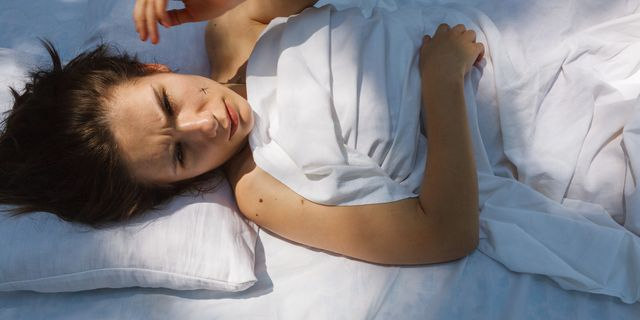 jonge vrouw ligt in bed en heeft last van muggen