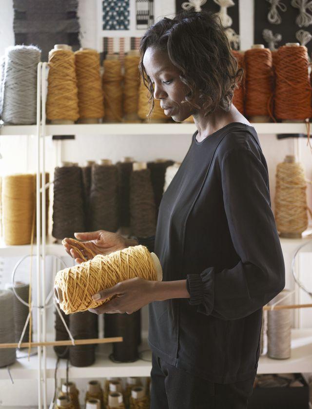 art director of merida sylvie johnson inspects a spool of golden yarn in a studio