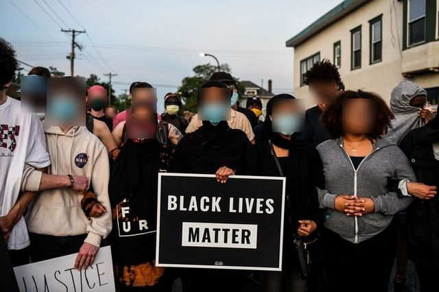 protesters hold a black lives matter sign their faces are blurred