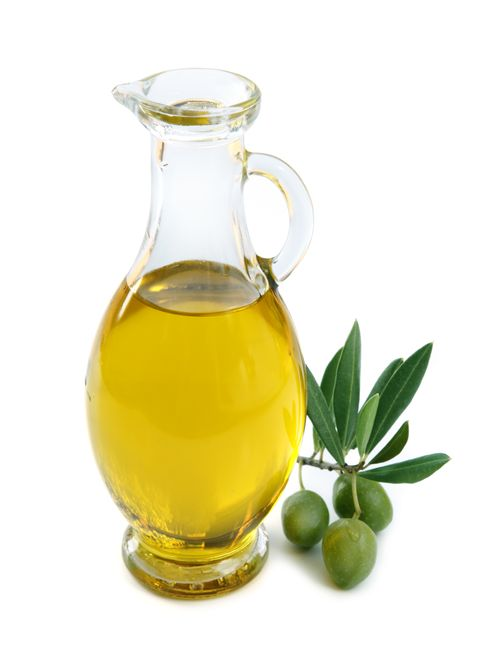 Jug of olive oil with 3 olives by the side