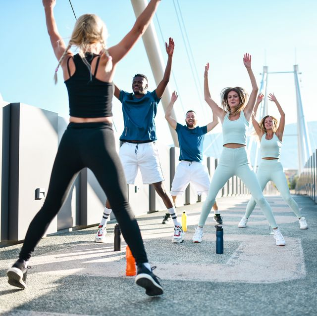 jumping jacks by female fitness instructor while working with multiethnic group outside