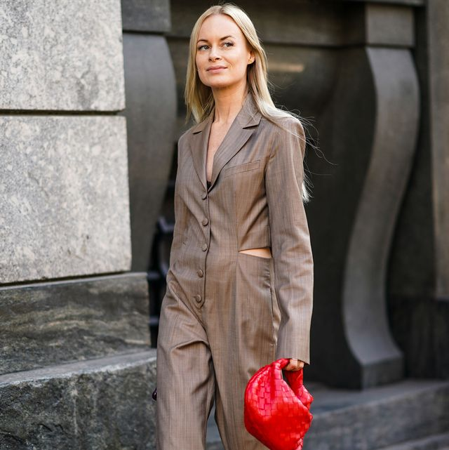 milan, italy   february 22 thora valdimars wears earrings, a brown full length wide legs jumpsuit with a slot at the waist, green nacreous pointy pumps, a red woven leather handbag , outside philosophy, during milan fashion week fallwinter 2020 2021 on february 22, 2020 in milan, italy photo by edward berthelotgetty images