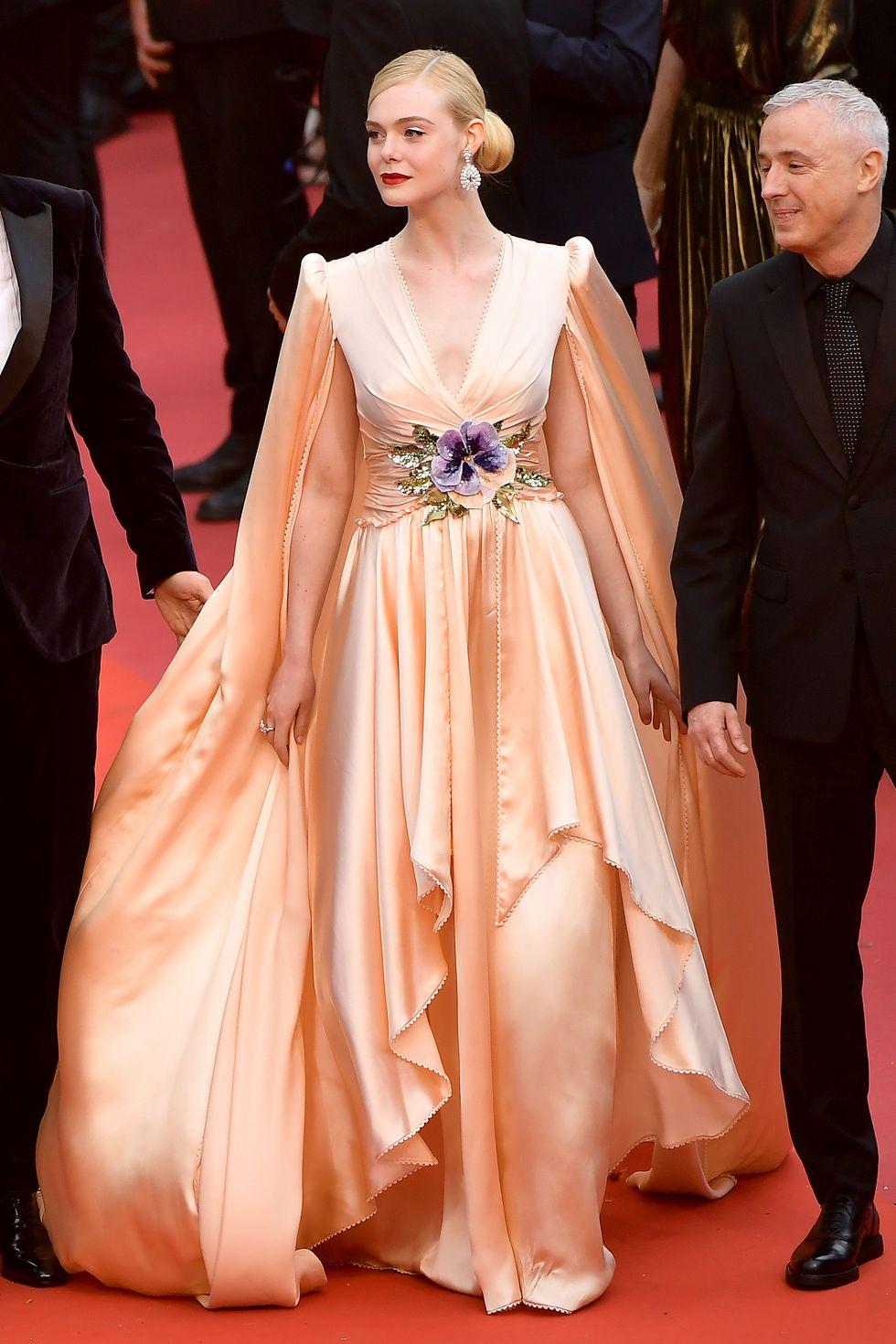 Fanning memakai gaun silk beraksen cape warna nude peach dari rumah mode ternama, Gucci