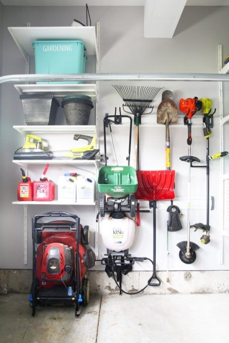 """interior of garage, with wall lined with gardening equipment including weed wacker, rake, shovel and green storage bin that reads """"gardening"""""""