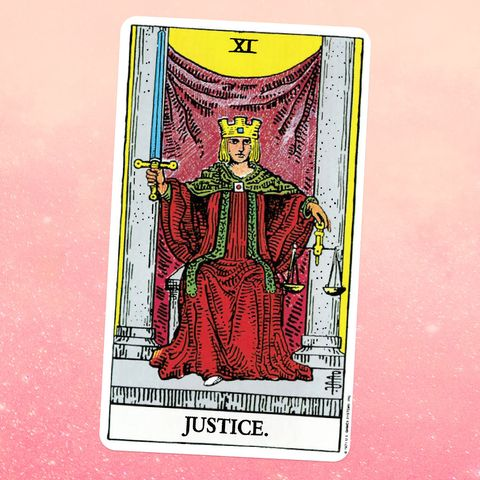 the tarot card justice, showing a person in a robe and crown, holding a sword, sitting on a throne