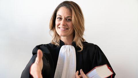 vrouwelijke rechter glimlacht en steekt hand uit
