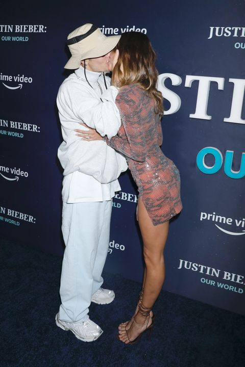 justin and hailey bieber kissing on a red carpet