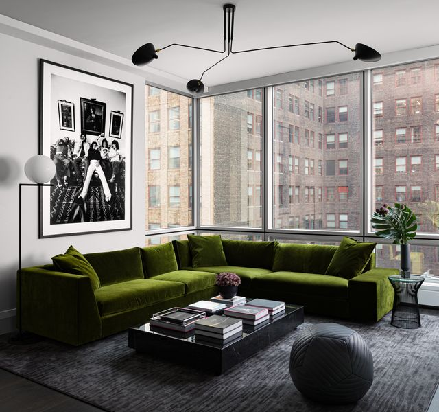 living room, green couch, dark gray rug, black and white wall art