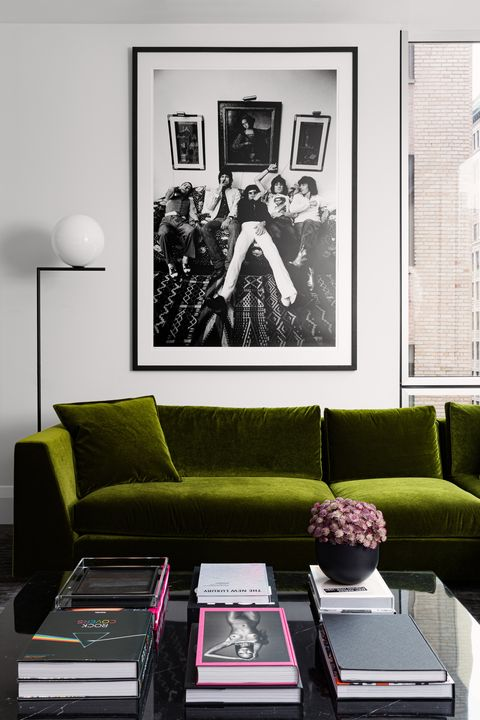 living room, green couch, coffee table, coffee table books, black and white wall print