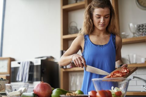 Young woman at kitchen table slicing tomatoes