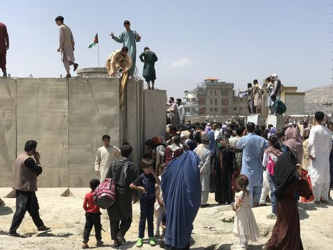 people struggle to cross the boundary wall of hamid karzai international airport to flee the country after rumors that foreign countries are evacuating people even without visas, after the taliban over run of kabul, afghanistan, 16 august 2021  photo by strnurphoto via getty images