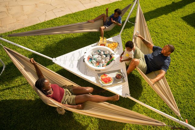 a family sitting in hammocks arond a table with food and drinks
