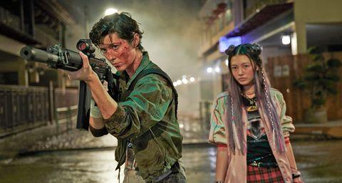mary elizabeth winstead apunta con un arma al frente mientras miku martineau queda un paso por detrás de ella en una escena de la película kate de netflix
