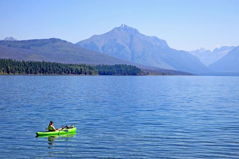 kayaker floats alone in lake mcdonald in summer in glacier national park montana