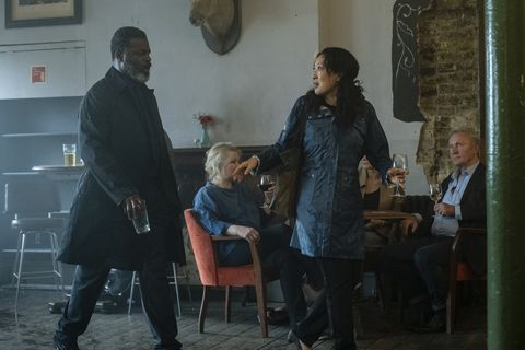 Danny Sapani and Sandra Oh in a scene from 'Killing Eve.' They are having an argument in a bar where Kenny's funeral is being heldand Eve is walking away.