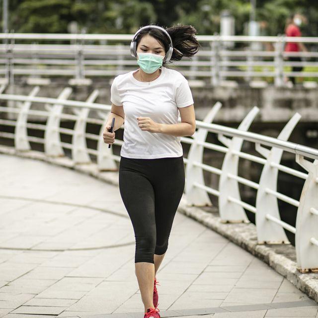 mujer corriendo en la calle con una mascarilla