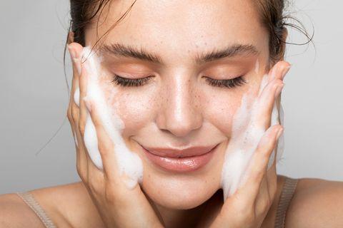 Chica limpiándose la cara con una mousse