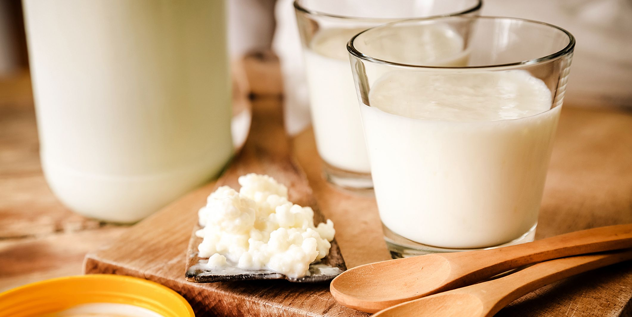 Kefir Grains In Wooden Spoon With Glass Of Kefir