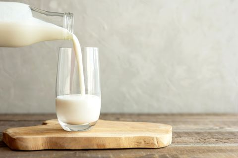 kefir, milk or turkish ayran drink are poured into a glass cup from a bottle a glass stands on a wooden stand on a rustic wooden table place for text