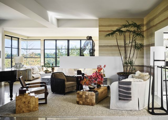 huge windows in the corner of the room let in natural light and the room is decorateed with mostly warm neutral colors