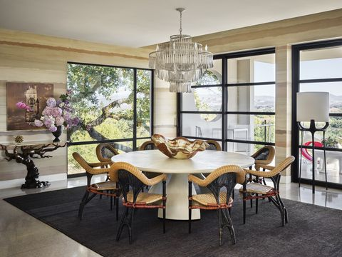 a hand painted wall mural depicts the tonal beauty of rammed earth and envelops a round dining table with chairs and a fancy chandelier hanging overhead