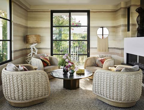 a quartet of braided swivel chairsforms an intimate fireside sitting room and surrounds a brass and pewter 1960s table