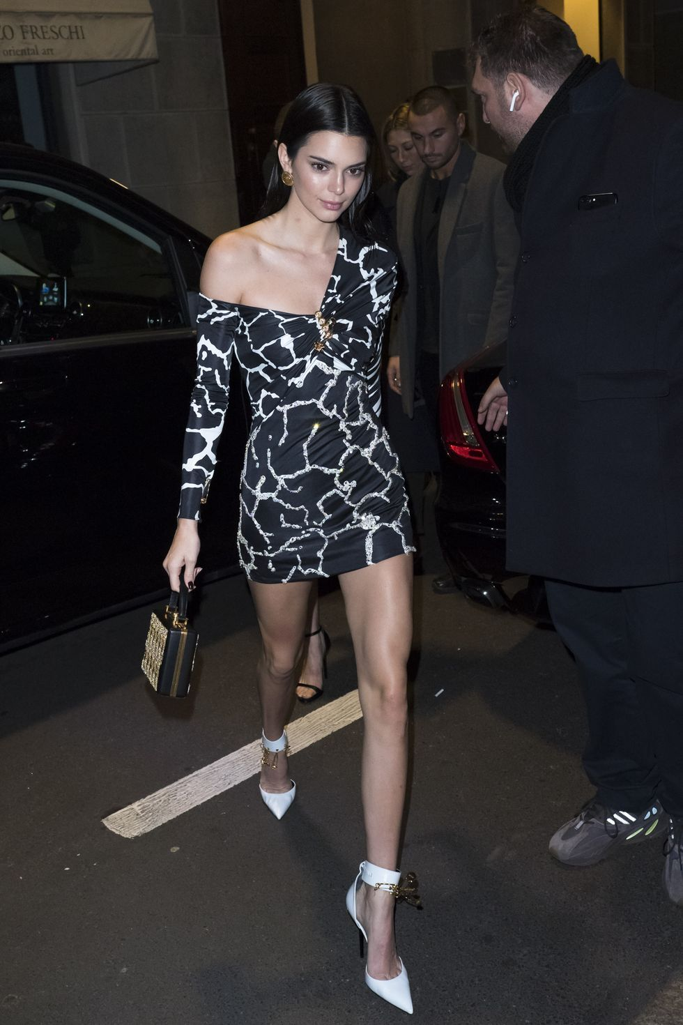 February 22, 2019 Kendall made her entrance at the Versace dinner during Milan Fashion Week in a black-and-white printed one-shoulder dress and white heels.