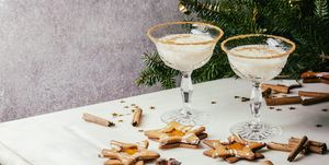 Eggnog Christmas milk cocktail, served in two vintage crystal glasses with shortbread star shape sugar cookies, cinnamon sticks, fir branch over white marble table.