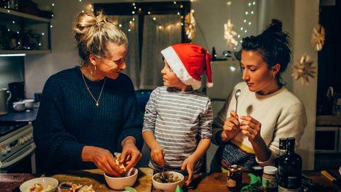 Twee vrouwen en een jongetje bereiden het kerstdiner voor