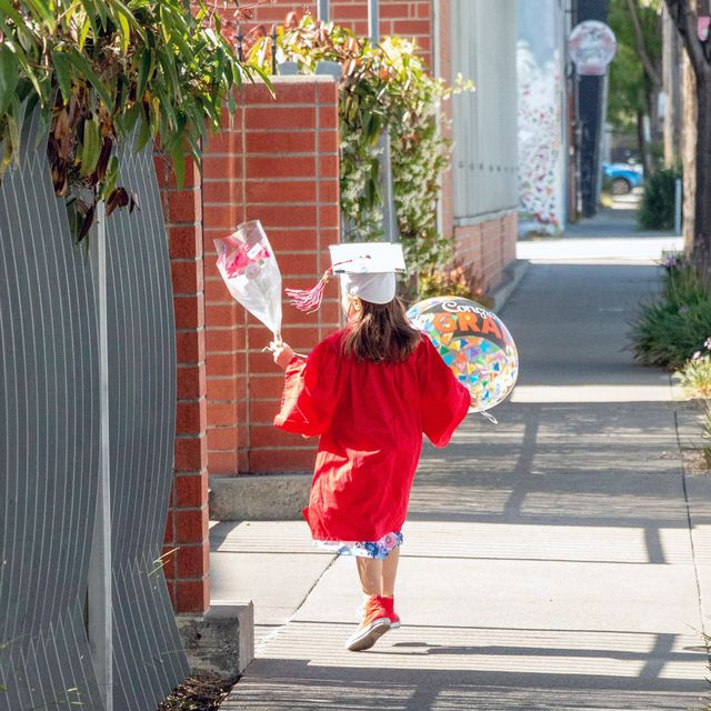 kid graduate carrying balloon and flowers
