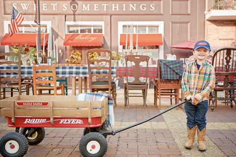 a child in cowboy boots dragging a red wagon down a main street
