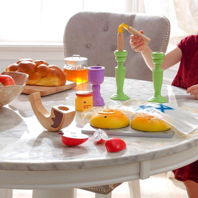 girl playing with kidkraft wooden rosh hashanah toy set