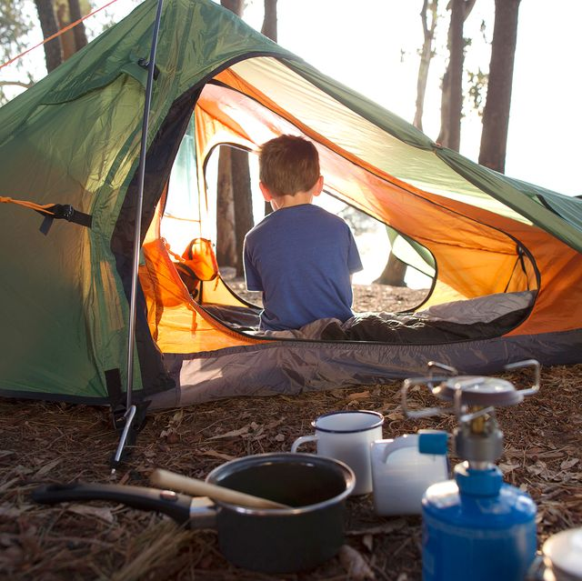 kid sitting in tent with camping supplies