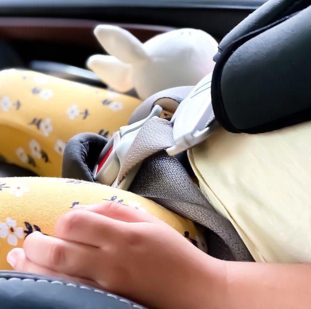 kid holding stuffed animal in car seat