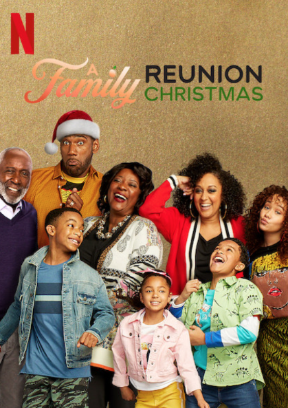 a black family with the dad wearing a santa hat and all are laughing