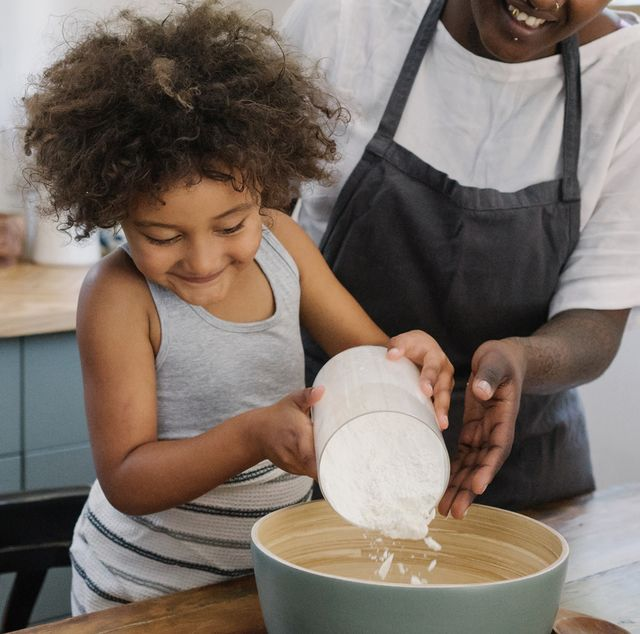 young girl pouring flour into a mixing bowl with mom helping